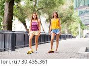 Купить «teenage girls with short skateboards in city», фото № 30435361, снято 19 июля 2018 г. (c) Syda Productions / Фотобанк Лори