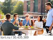 Купить «happy friends with drinks or bbq party on rooftop», фото № 30435389, снято 2 сентября 2018 г. (c) Syda Productions / Фотобанк Лори
