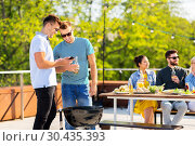 Купить «happy friends grilling at bbq party on rooftop», фото № 30435393, снято 2 сентября 2018 г. (c) Syda Productions / Фотобанк Лори