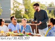 Купить «friends at bbq party on rooftop in summer», фото № 30435397, снято 2 сентября 2018 г. (c) Syda Productions / Фотобанк Лори