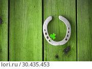 Купить «horseshoe with shamrock on green wood boards», фото № 30435453, снято 31 января 2018 г. (c) Syda Productions / Фотобанк Лори