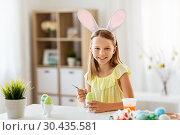 Купить «happy girl coloring easter eggs at home», фото № 30435581, снято 25 июля 2018 г. (c) Syda Productions / Фотобанк Лори