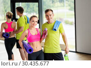 Купить «couple with bottles, exercise mat and towel in gym», фото № 30435677, снято 29 июня 2014 г. (c) Syda Productions / Фотобанк Лори