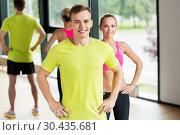 Купить «smiling man and woman exercising in gym», фото № 30435681, снято 29 июня 2014 г. (c) Syda Productions / Фотобанк Лори