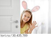 Купить «happy girl with easter bunny ears peeking out door», фото № 30435789, снято 25 июля 2018 г. (c) Syda Productions / Фотобанк Лори