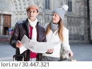 Купить «Smiling couple man and woman with map», фото № 30447321, снято 18 ноября 2017 г. (c) Яков Филимонов / Фотобанк Лори