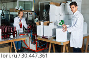 Купить «Man standing in packing section on winemaking factory», фото № 30447361, снято 21 сентября 2016 г. (c) Яков Филимонов / Фотобанк Лори