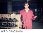 Купить «smiling man wearing uniform working with bottle storage racks», фото № 30447369, снято 21 сентября 2016 г. (c) Яков Филимонов / Фотобанк Лори