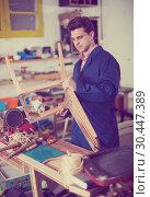 Купить «Man carpenter in furniture repair workshop», фото № 30447389, снято 8 апреля 2017 г. (c) Яков Филимонов / Фотобанк Лори