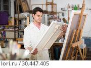 Купить «Man near easel painting on canvas», фото № 30447405, снято 8 апреля 2017 г. (c) Яков Филимонов / Фотобанк Лори