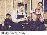 Купить «Brunette getting haircutting from two hairstylists», фото № 30447429, снято 5 марта 2018 г. (c) Яков Филимонов / Фотобанк Лори