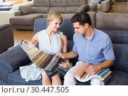Купить «Family of two are choosing color of new sofa», фото № 30447505, снято 19 июня 2017 г. (c) Яков Филимонов / Фотобанк Лори