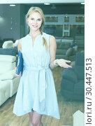 Купить «Seller female is demonstrating prices for sofa», фото № 30447513, снято 19 июня 2017 г. (c) Яков Филимонов / Фотобанк Лори