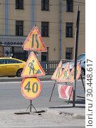 """Купить «Ведутся дорожные работы. На проезжей части стоят дорожные знаки """"Сужение дороги справа"""", """"Дорожные работы"""", """"Ограничение скорости""""», фото № 30448617, снято 27 марта 2019 г. (c) Наталья Николаева / Фотобанк Лори"""