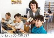 Купить «Woman teacher helping boy in computer room», фото № 30450797, снято 19 декабря 2018 г. (c) Яков Филимонов / Фотобанк Лори