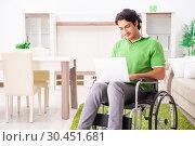 Купить «Young handsome man in wheelchair at home», фото № 30451681, снято 14 ноября 2018 г. (c) Elnur / Фотобанк Лори