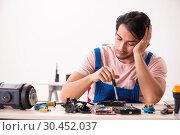 Купить «Young male contractor repairing computer», фото № 30452037, снято 28 ноября 2018 г. (c) Elnur / Фотобанк Лори