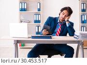 Купить «Young handsome businessman sitting in the office», фото № 30453517, снято 28 ноября 2018 г. (c) Elnur / Фотобанк Лори