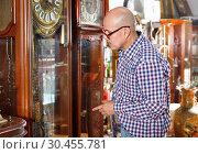 Купить «Portrait of mature man choosing vintage goods at antiques shop», фото № 30455781, снято 15 мая 2018 г. (c) Яков Филимонов / Фотобанк Лори