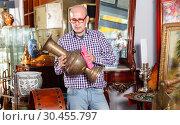 Купить «Middle aged man owner of antiques shop wiping vintage goods», фото № 30455797, снято 15 мая 2018 г. (c) Яков Филимонов / Фотобанк Лори