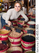 Купить «Beautiful female customer selecting dried beans», фото № 30455905, снято 19 апреля 2019 г. (c) Яков Филимонов / Фотобанк Лори