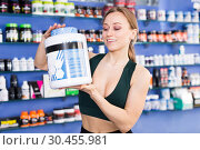 Купить «Young fit woman with pot of sports nutritional products», фото № 30455981, снято 12 апреля 2018 г. (c) Яков Филимонов / Фотобанк Лори