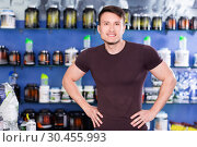 Купить «Portrait of young muscular man on background with shelves of sport nutrition products», фото № 30455993, снято 12 апреля 2018 г. (c) Яков Филимонов / Фотобанк Лори