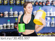 Купить «Fit girl looking happy choosing sports nutritional food in shop», фото № 30455997, снято 12 апреля 2018 г. (c) Яков Филимонов / Фотобанк Лори