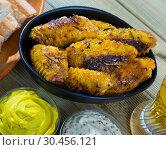 Купить «Fried chicken wings served in black bowl, fresh sauses on table», фото № 30456121, снято 28 мая 2020 г. (c) Яков Филимонов / Фотобанк Лори