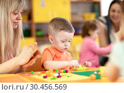 Купить «Children at lesson in kindergarten. Baby toddler playing with plasticine with teacher in nursery playroom.», фото № 30456569, снято 26 августа 2019 г. (c) Оксана Кузьмина / Фотобанк Лори
