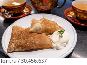 Купить «Pancakes with sour cream and tea in traditional dish for holiday Maslenitsa», фото № 30456637, снято 9 марта 2019 г. (c) Володина Ольга / Фотобанк Лори