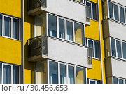 Купить «Fragment of brightly colored apartment building with balconies», фото № 30456653, снято 4 июня 2018 г. (c) Володина Ольга / Фотобанк Лори