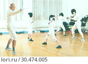 Купить «Coaches demonstrating to young athletes attack movements with rapier during fencing workout», фото № 30474005, снято 30 мая 2018 г. (c) Яков Филимонов / Фотобанк Лори