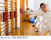 Купить «Group practicing fencing techniques in gym», фото № 30474013, снято 30 мая 2018 г. (c) Яков Филимонов / Фотобанк Лори