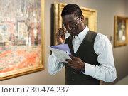 Купить «Afro man visiting exposition», фото № 30474237, снято 19 января 2019 г. (c) Яков Филимонов / Фотобанк Лори