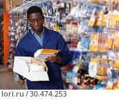 Купить «salesman arranging different goods on stand in shop», фото № 30474253, снято 21 января 2019 г. (c) Яков Филимонов / Фотобанк Лори