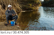Купить «Man fishing with rods on river», фото № 30474305, снято 27 января 2019 г. (c) Яков Филимонов / Фотобанк Лори