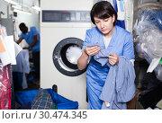 Купить «Female laundry worker sorting dirty clothes», фото № 30474345, снято 15 января 2019 г. (c) Яков Филимонов / Фотобанк Лори