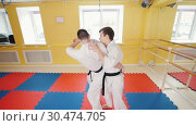Two men training their aikido skills. A man grabs his opponent and throws him over. Стоковое видео, видеограф Константин Шишкин / Фотобанк Лори