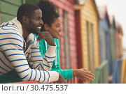 Couple interacting with each other at beach hut . Стоковое фото, агентство Wavebreak Media / Фотобанк Лори
