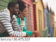 Купить «Couple interacting with each other at beach hut », фото № 30475537, снято 14 ноября 2018 г. (c) Wavebreak Media / Фотобанк Лори