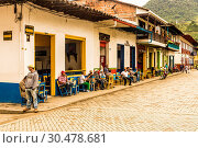 Купить «Local people socialising on the main square, with its preserved, colourful, colonial buildings, Jardin, Colombia, South America», фото № 30478681, снято 20 апреля 2018 г. (c) age Fotostock / Фотобанк Лори