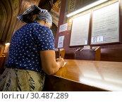 Купить «Женщина в храме пишет церковную записку», фото № 30487289, снято 22 августа 2018 г. (c) Вячеслав Палес / Фотобанк Лори