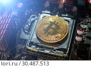 Golden bitcoin lying on the electronic computer component. Business concept of bitcoin mining and digital cryptocurrency. Blockchain technology, bitcoin mining concept. Стоковое фото, фотограф Зезелина Марина / Фотобанк Лори