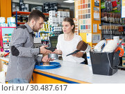 Купить «Girl seller standing at the counter and consulting man», фото № 30487617, снято 17 мая 2018 г. (c) Яков Филимонов / Фотобанк Лори
