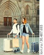 Купить «Young couple man and woman going the historic city center», фото № 30487693, снято 25 мая 2017 г. (c) Яков Филимонов / Фотобанк Лори
