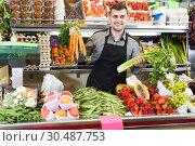 Купить «Adult man seller is displaying assortment», фото № 30487753, снято 18 марта 2017 г. (c) Яков Филимонов / Фотобанк Лори