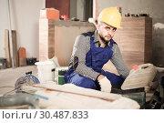 Купить «Worker is choosing tools in suitcase for work at the object.», фото № 30487833, снято 3 июня 2017 г. (c) Яков Филимонов / Фотобанк Лори