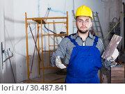 Купить «Professional in the helmet ready is plastering the wall», фото № 30487841, снято 3 июня 2017 г. (c) Яков Филимонов / Фотобанк Лори