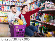 two attentive adult people in good spirits selecting detergents in the store. Стоковое фото, фотограф Яков Филимонов / Фотобанк Лори
